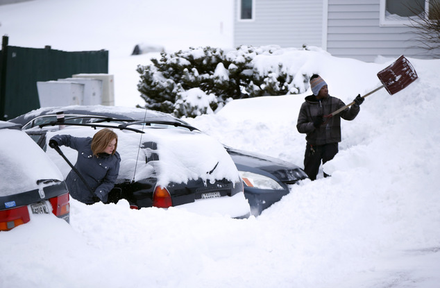 Neighbors at a Munjoy Hill apartment complex dig their cars out after a winter snow storm, Wednesday, Jan 27, 2015, in Portland, Maine. Tuesday's blizzard dumped about two feet of snow in Portland. (AP Photo/Robert F. Bukaty)